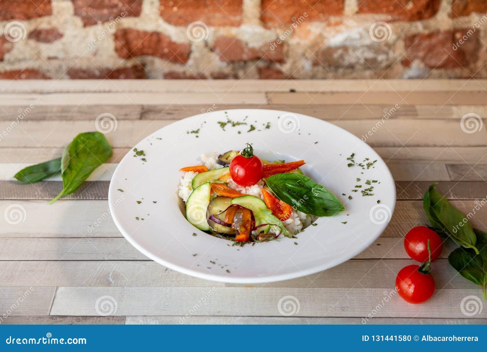 En vit platta med ris och nya grönsaker Ny mat för strikt vegetarian Garnering med oreganon och körsbärsröda tomater