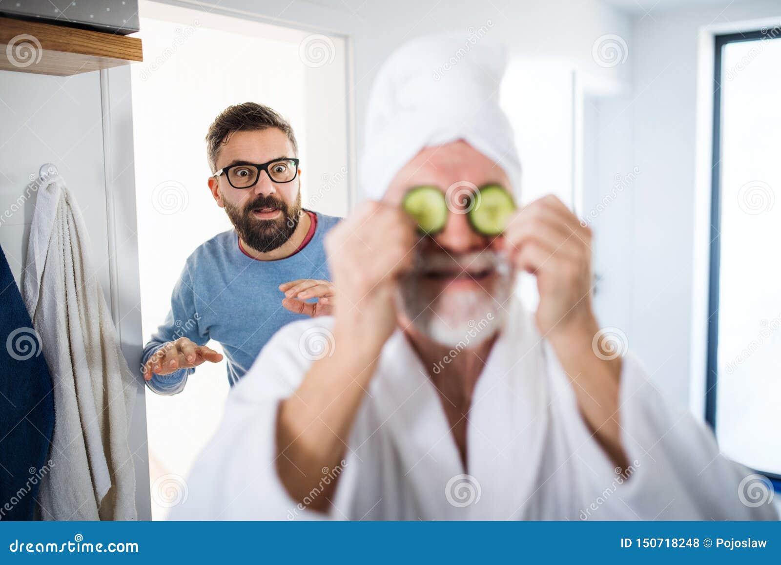 En vuxen hipsterson och en h?g fader i badrum inomhus hemma och att ha gyckel