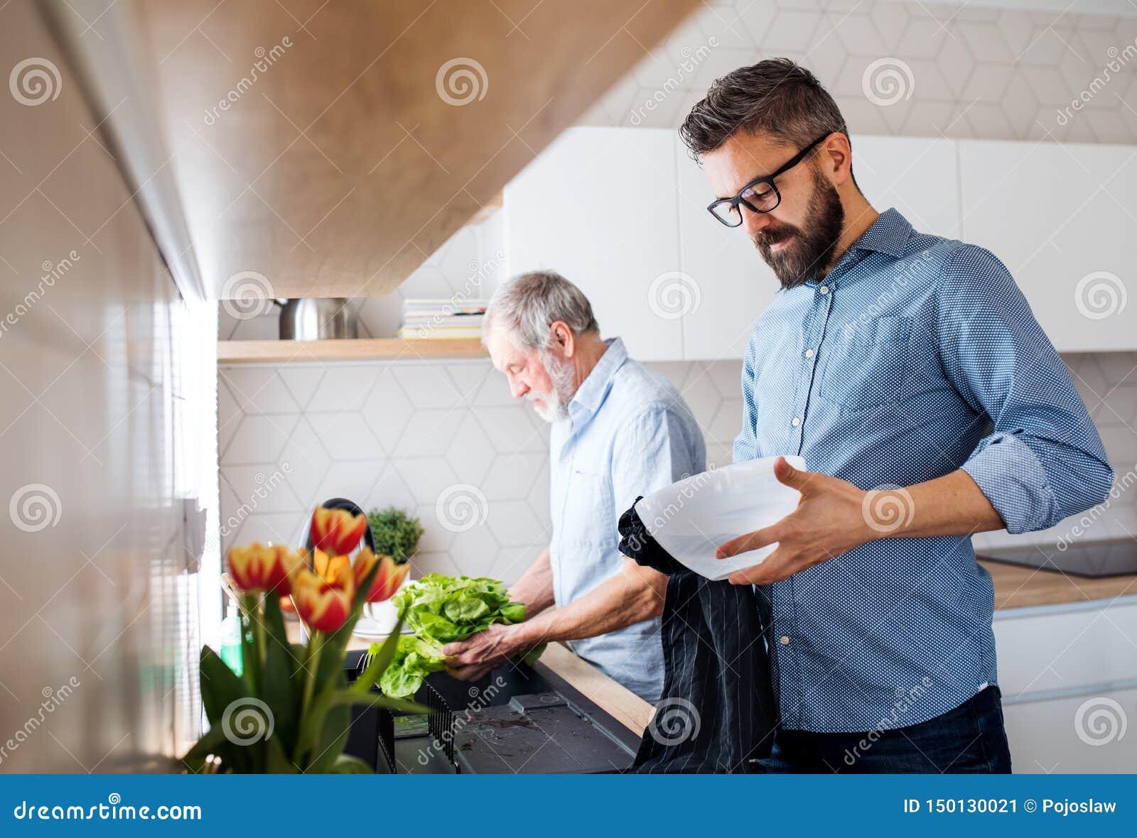 En vuxen hipsterson och en h?g fader inomhus hemma och att tv?tta gr?nsaker