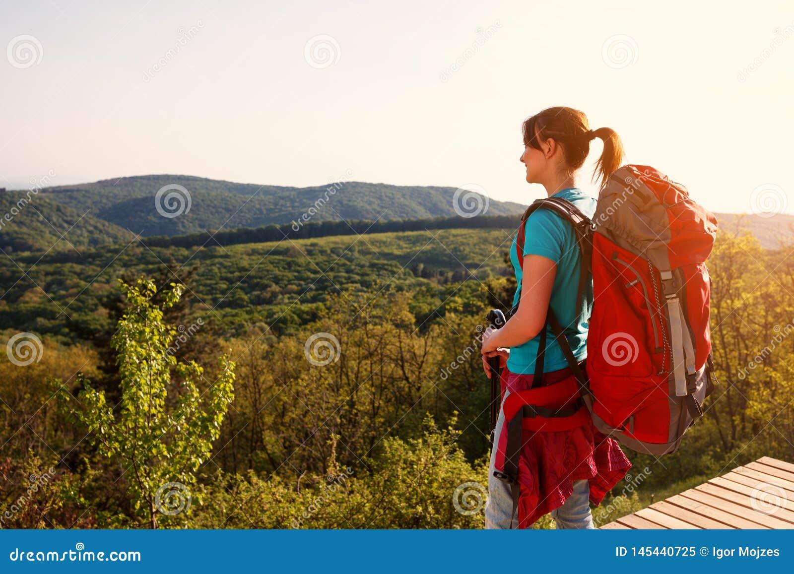 En wandelaarwijfje die panorama opstaan kijken