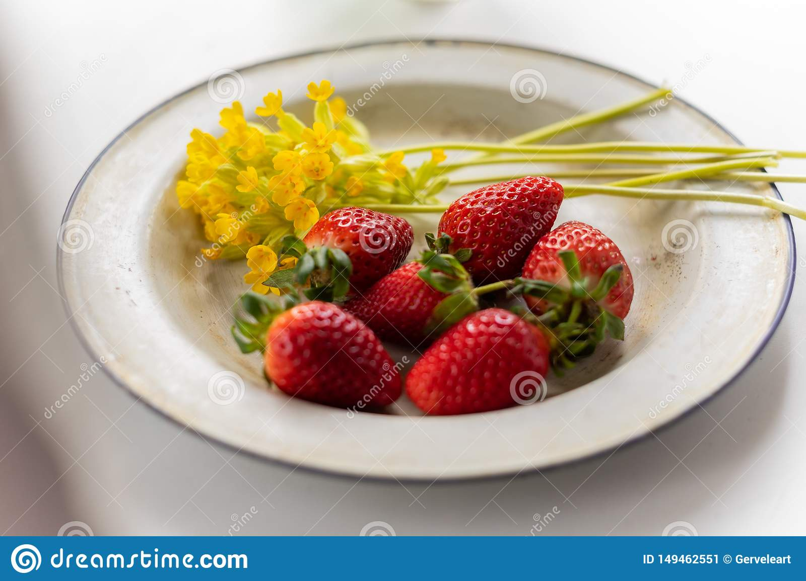 Enameled vintage plate with ripe strawberries and yellow flowers
