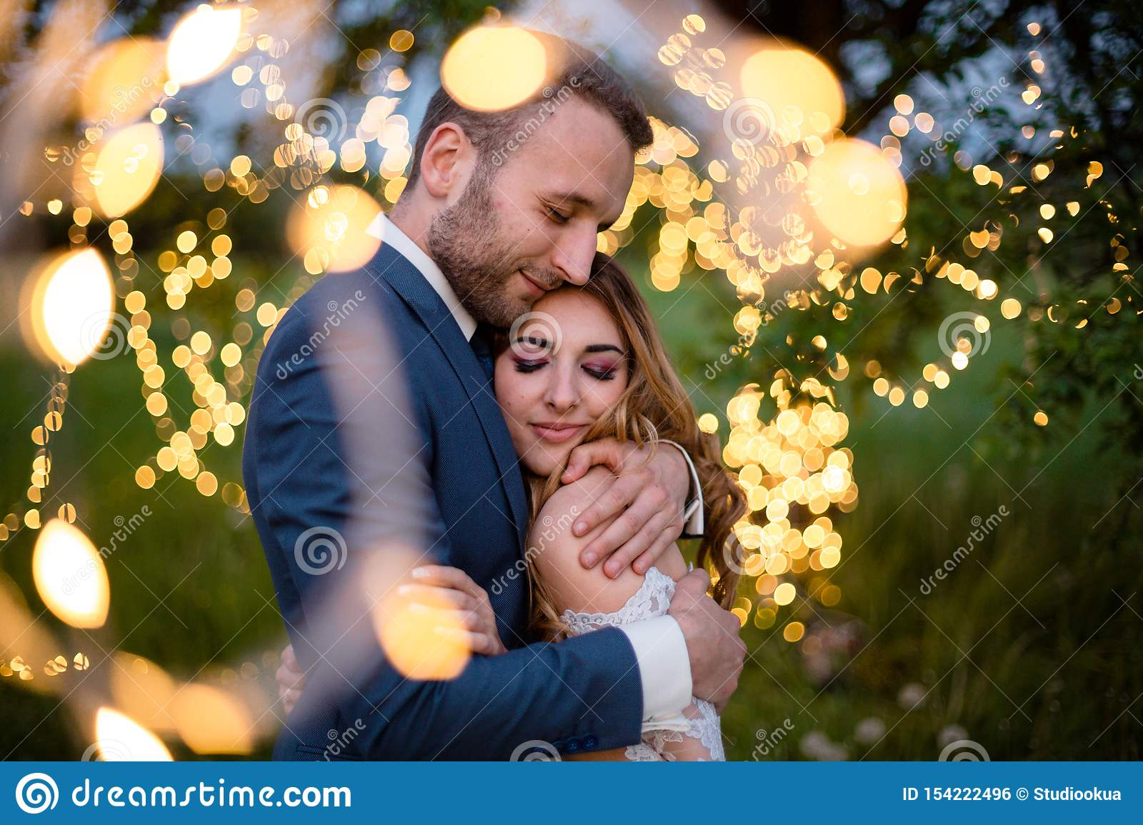 Enamored newlyweds gently embrace. Wedding ceremony in nature. The lights of the electric garland illuminate the wedding