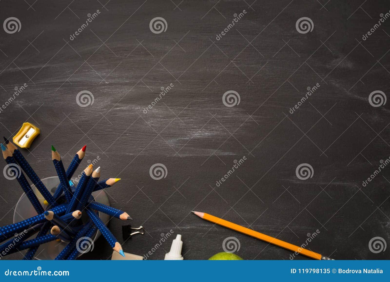 Encaissez le récipient avec les crayons et les fournitures de bureau colorés sur le panneau de craie noir