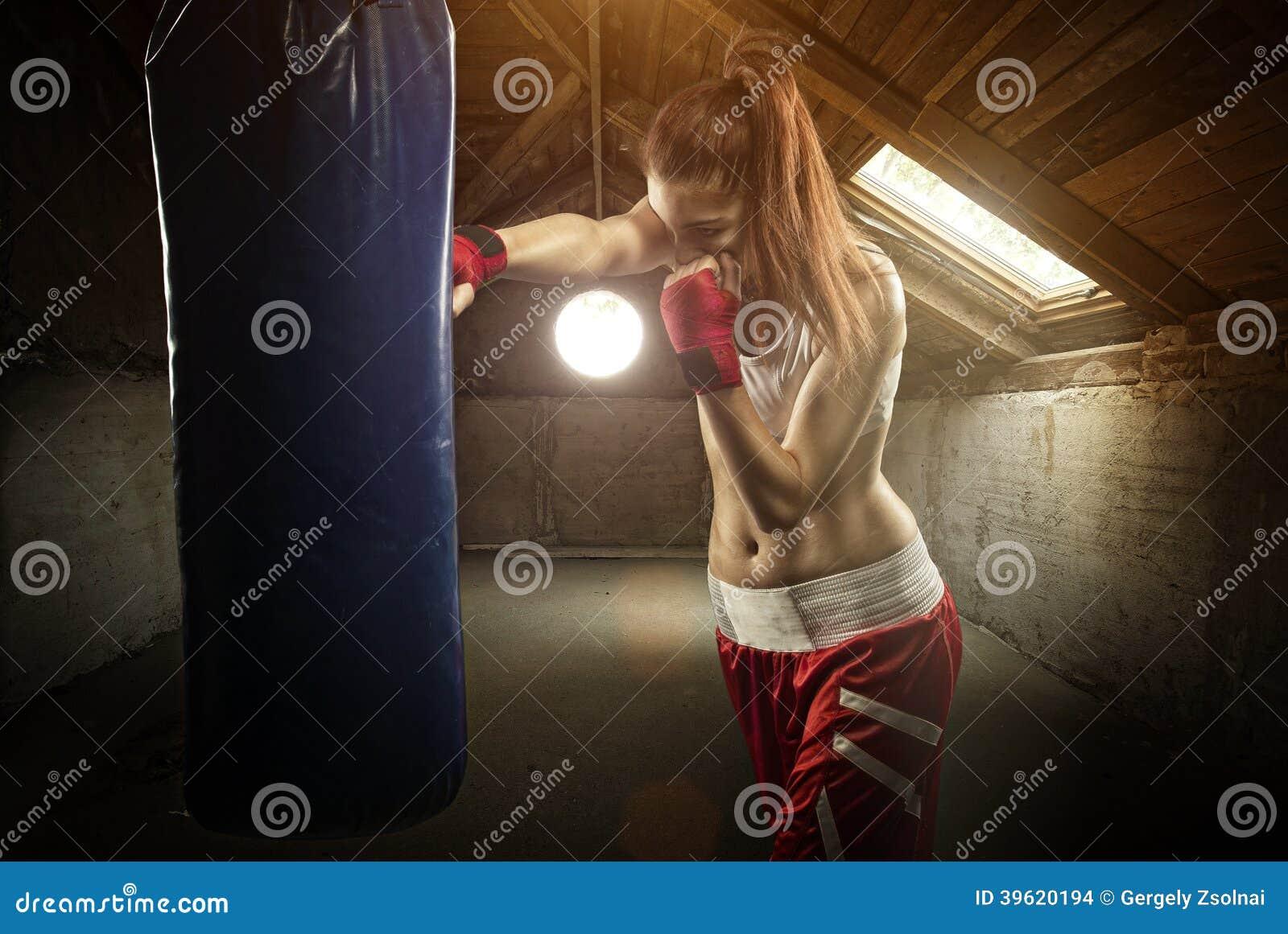 Encaixotamento das jovens mulheres, batendo o saco do encaixotamento - no sótão