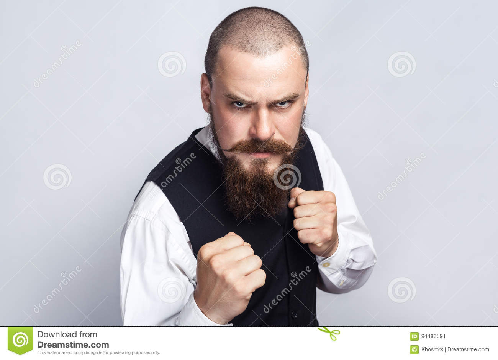 Encaixotamento irritado Homem de negócios considerável com o bigode da barba e do guiador que olha a câmera com cara e o punho ir