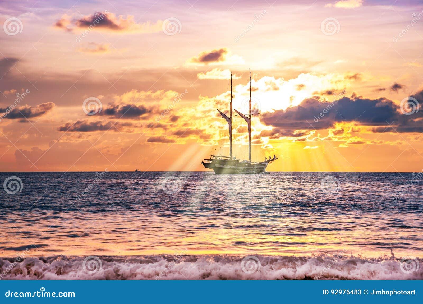 Encalhe a areia com o barco no crepúsculo e o por do sol e o raio de sol do mar