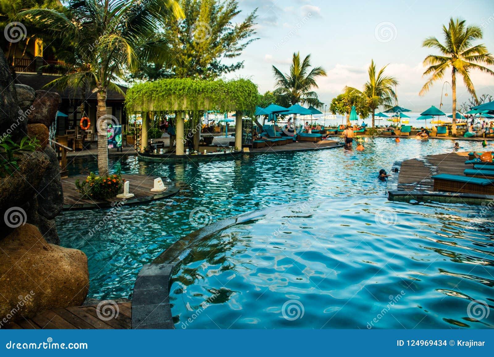 Encalhe sunbeds perto da piscina no recurso tropical com as palmas durante o por do sol, Gili Trawangan, Lombok, Indonésia