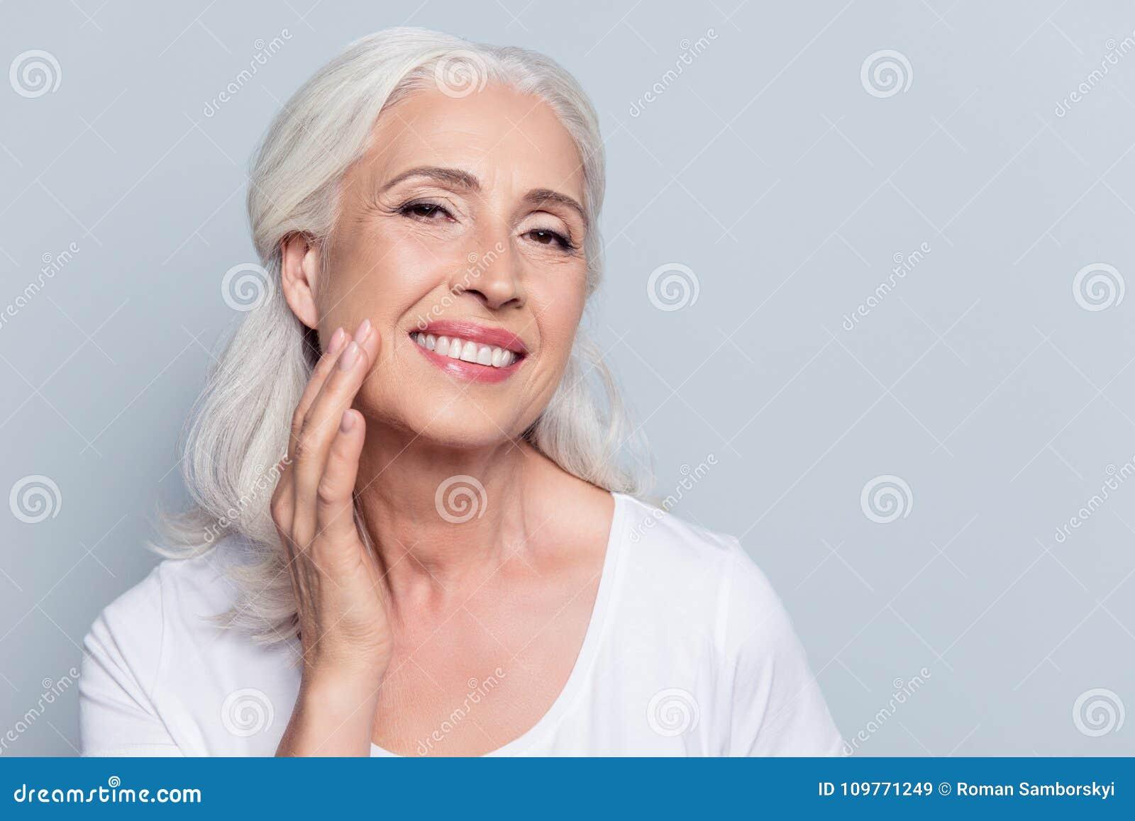 Encantamento, bonito, mulher adulta que toca em sua pele macia perfeita da cara