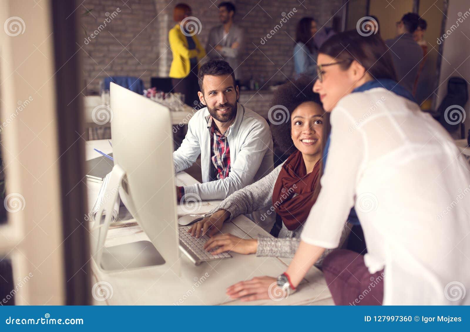 Encargado de sexo femenino que mira tarea de funcionamiento en el ordenador en oficina