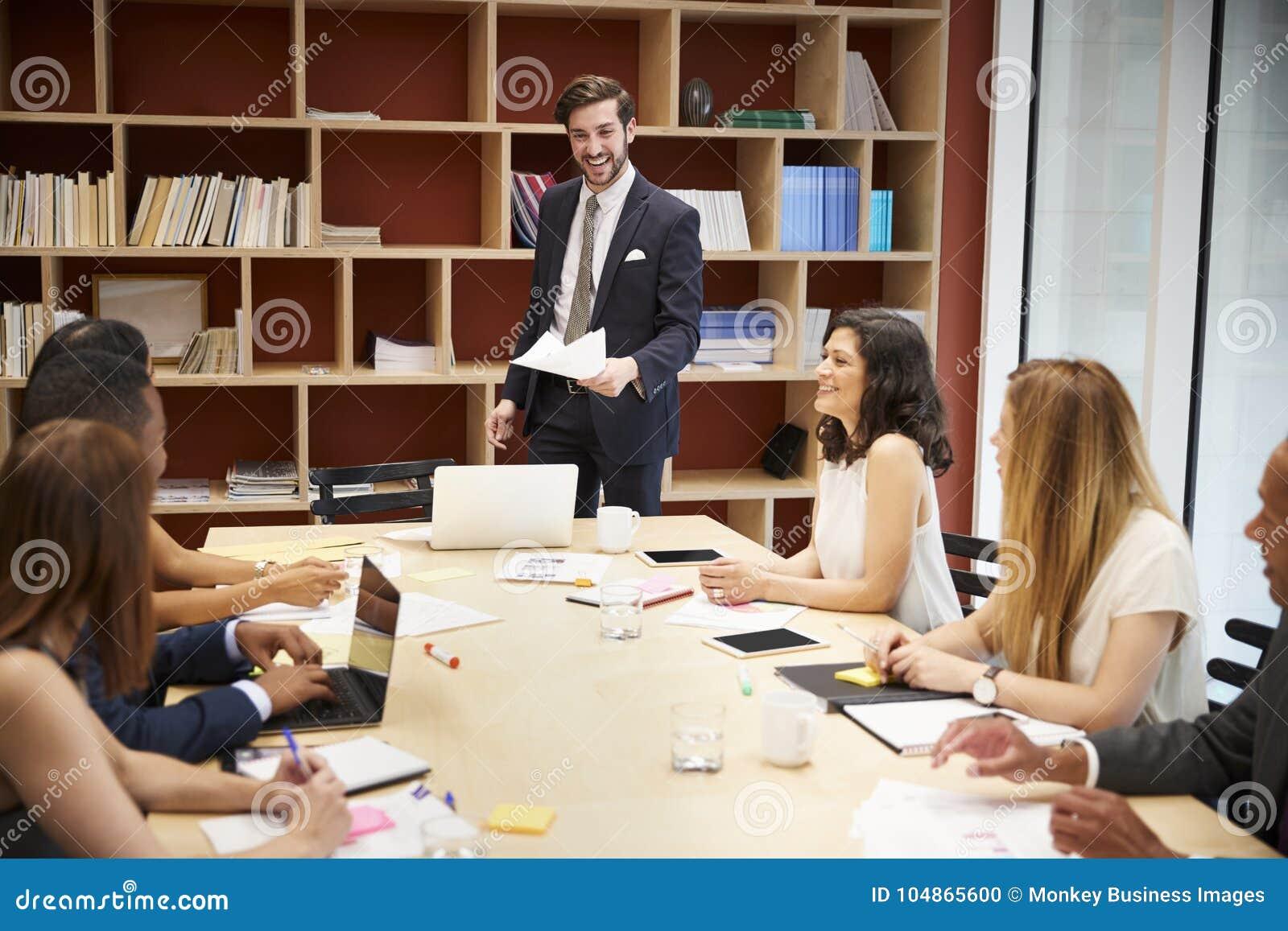 Encargado de sexo masculino joven que se coloca en una reunión de la sala de reunión del negocio
