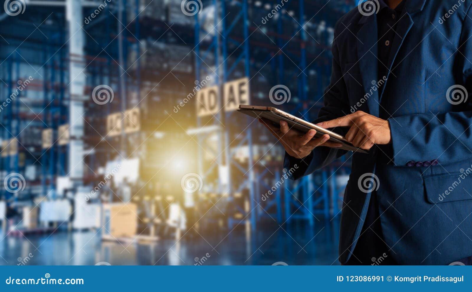 Encargado del hombre de negocios que usa el control y el control de la tableta para los trabajadores con el almacén comercial mod