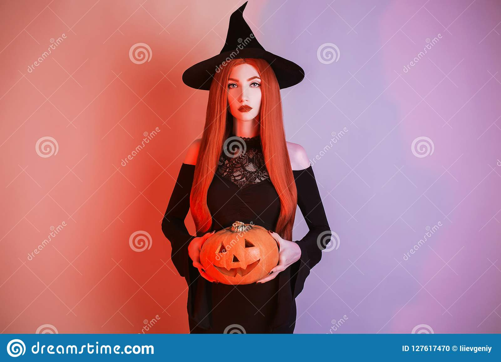 Enchanting halloween costume. Gothic woman witch with pale skin and red hair in black dress holding jack pumpkin. Girl witch with