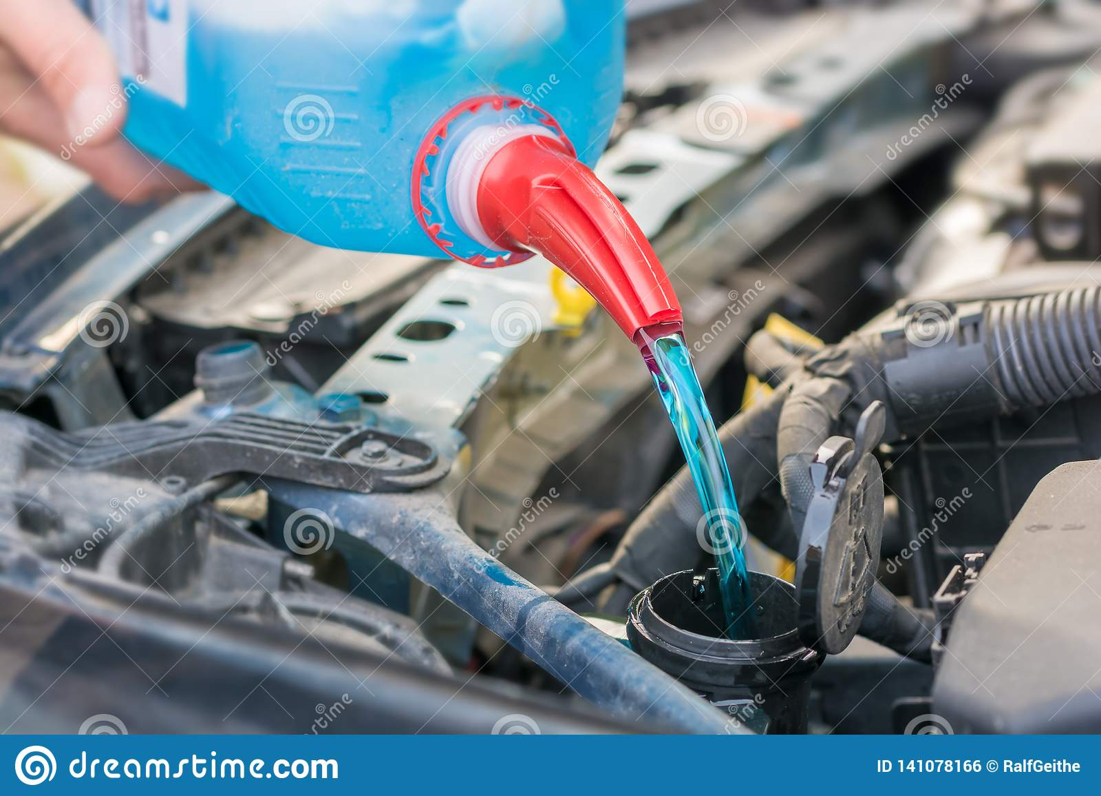Enchendo o tanque de água com o anticongelante no compartimento de motor de um carro