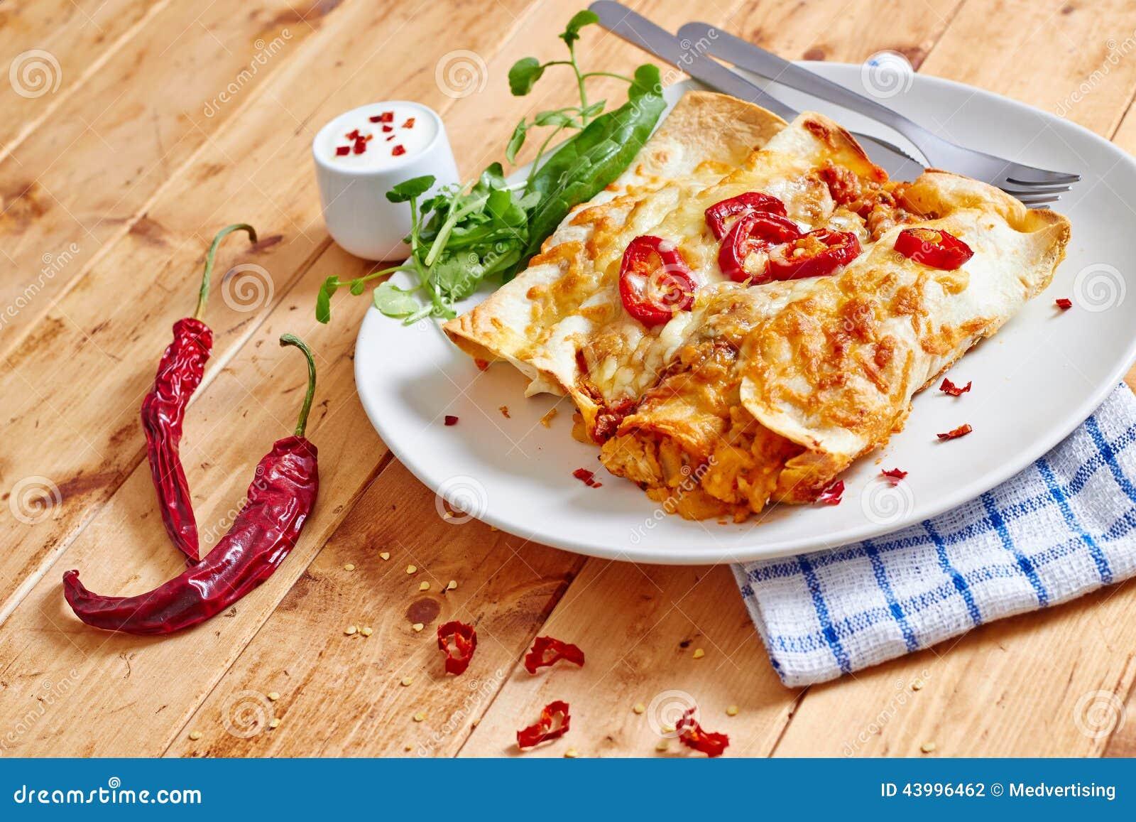 Enchiladas richten mit Vorderansicht der glühenden Paprikas an