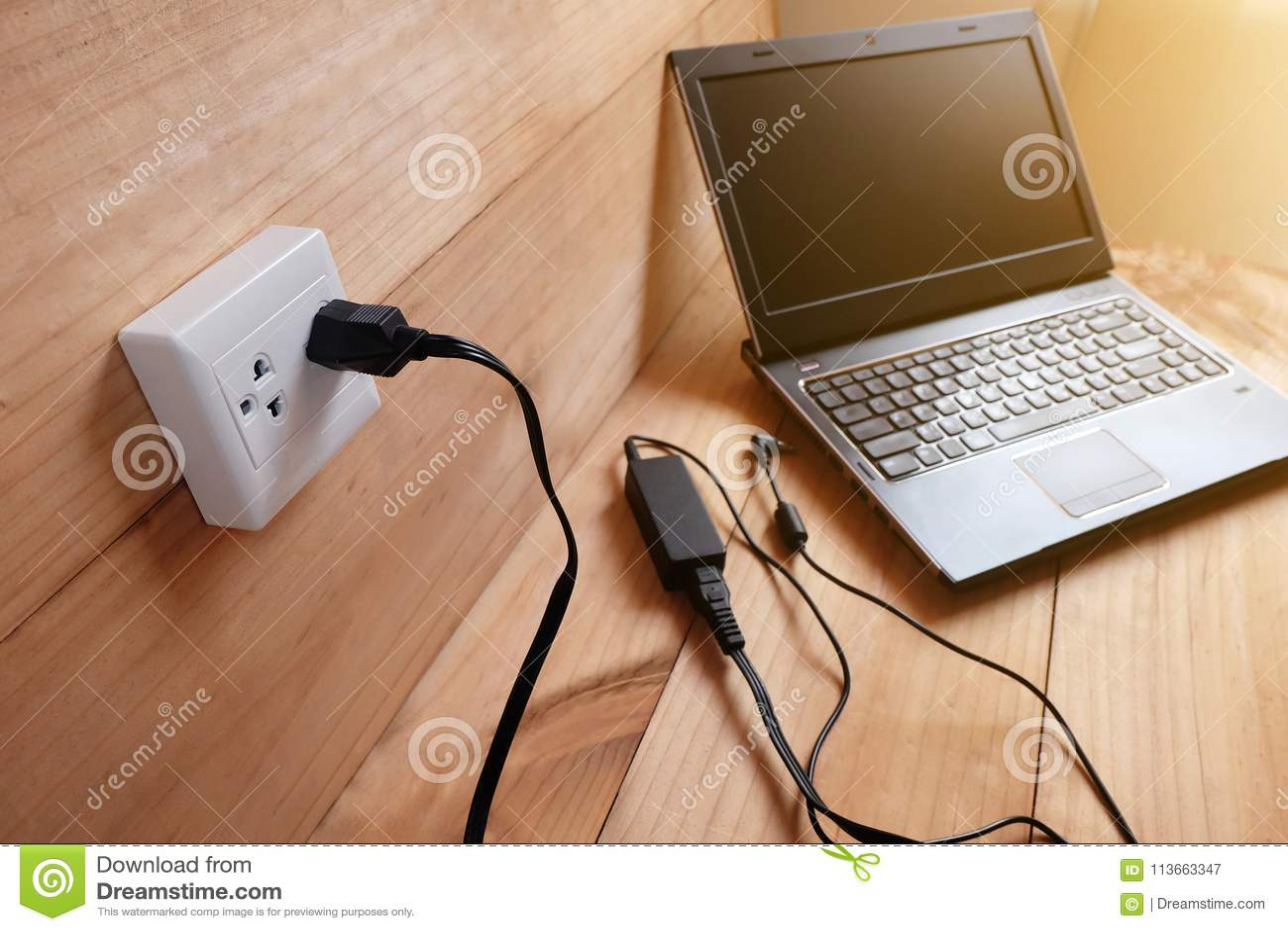 Enchufe el cargador del cable eléctrico del adaptador del ordenador portátil en piso de madera