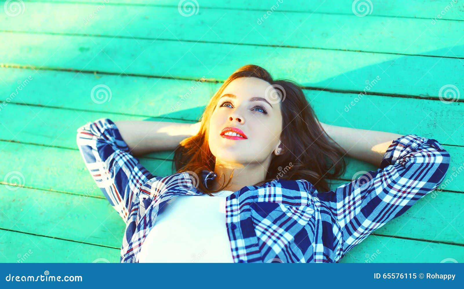 Encontro de descanso da jovem mulher feliz em um assoalho de madeira