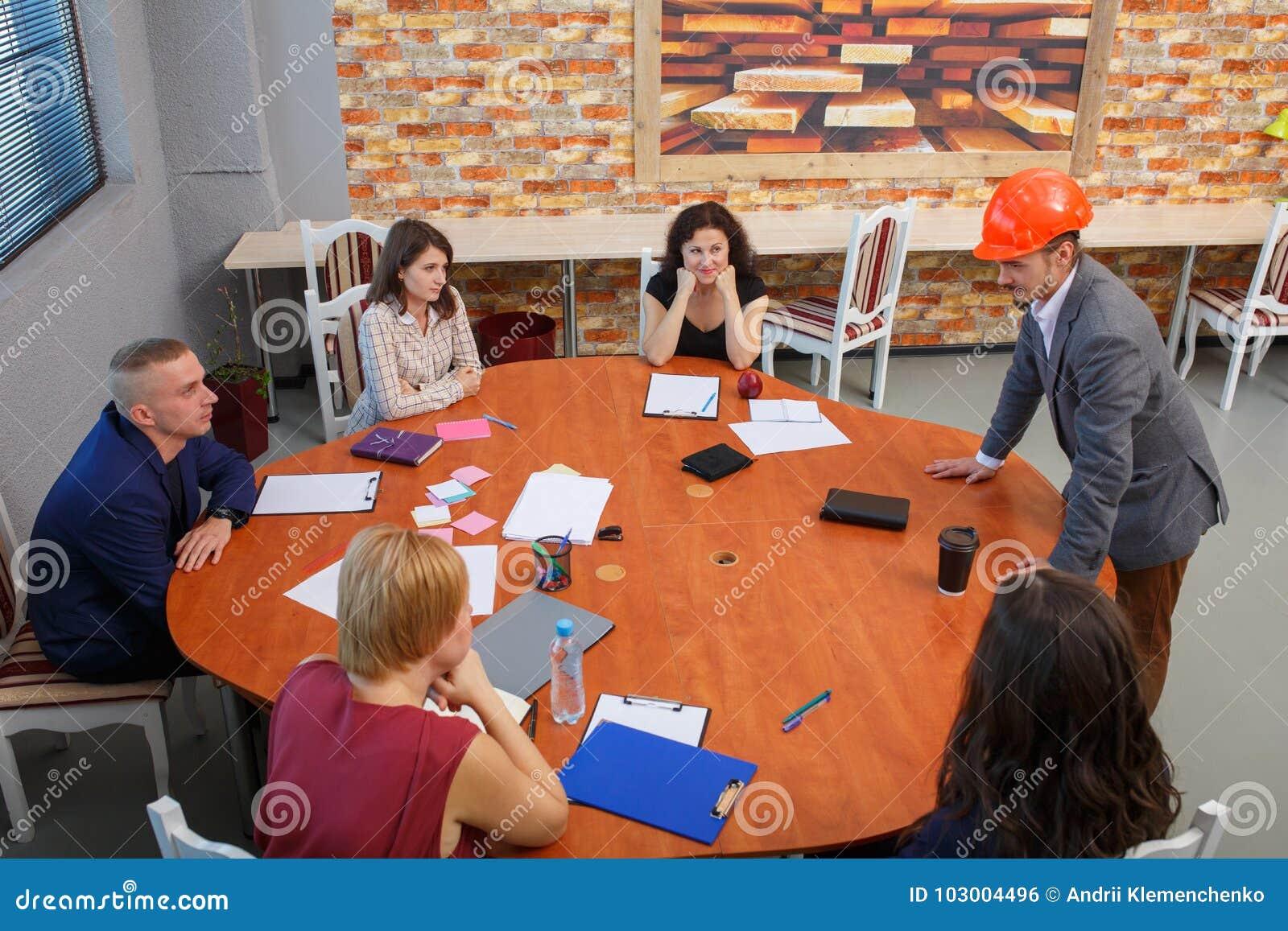 Encontro no escritório Na mesa redonda a equipe senta-se, e ao lado dela há um chefe em um capacete