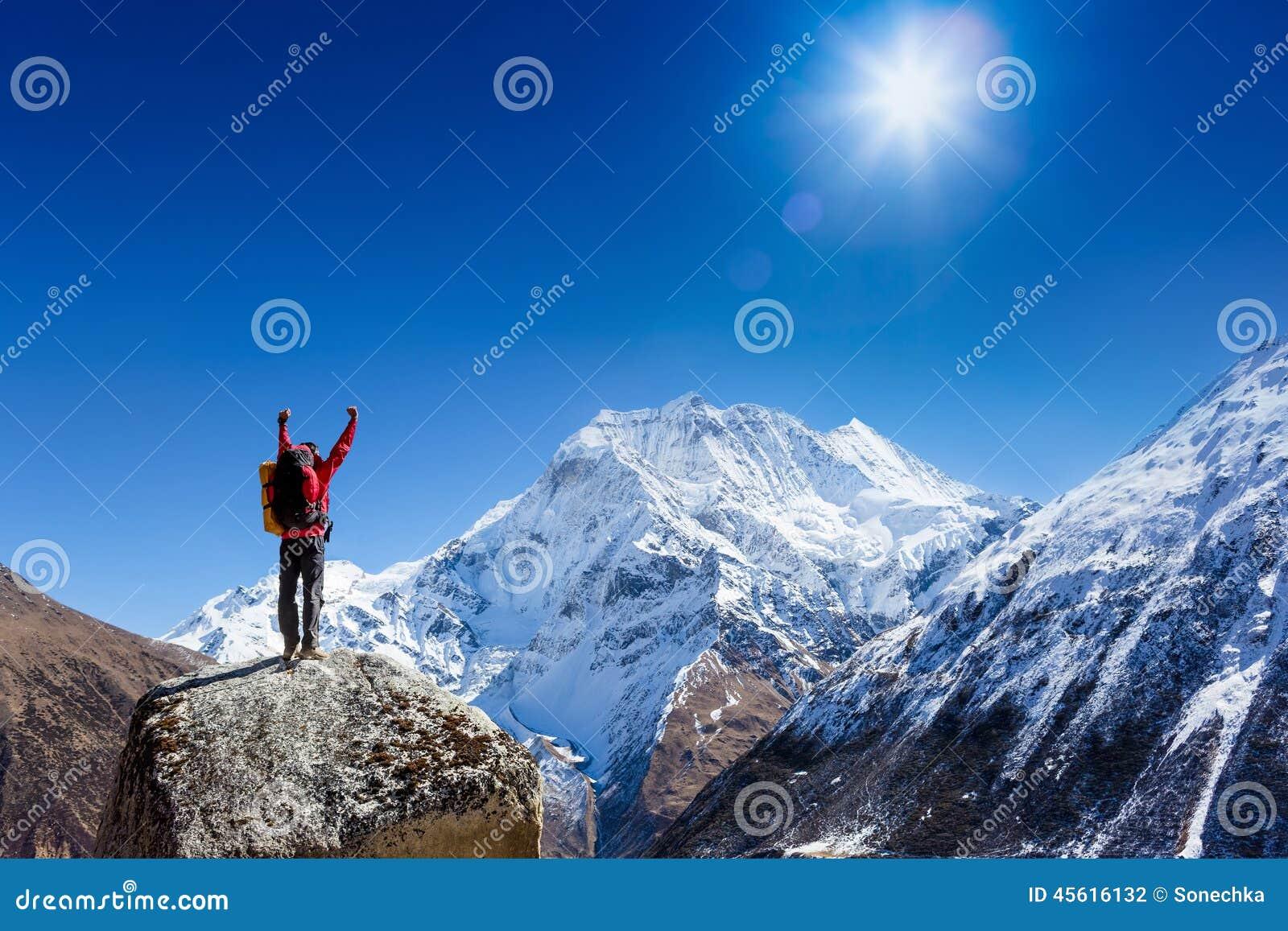 Encourager de randonneur exalté et heureux avec des bras a augmenté dans le ciel après la hausse au sommet de dessus de montagne
