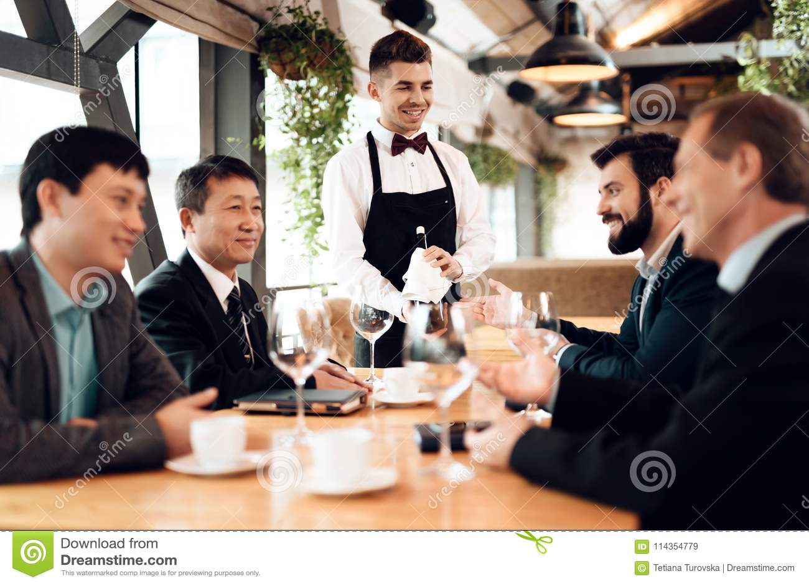 Encuentro con de hombres de negocios chinos en restaurante El camarero trae el vino