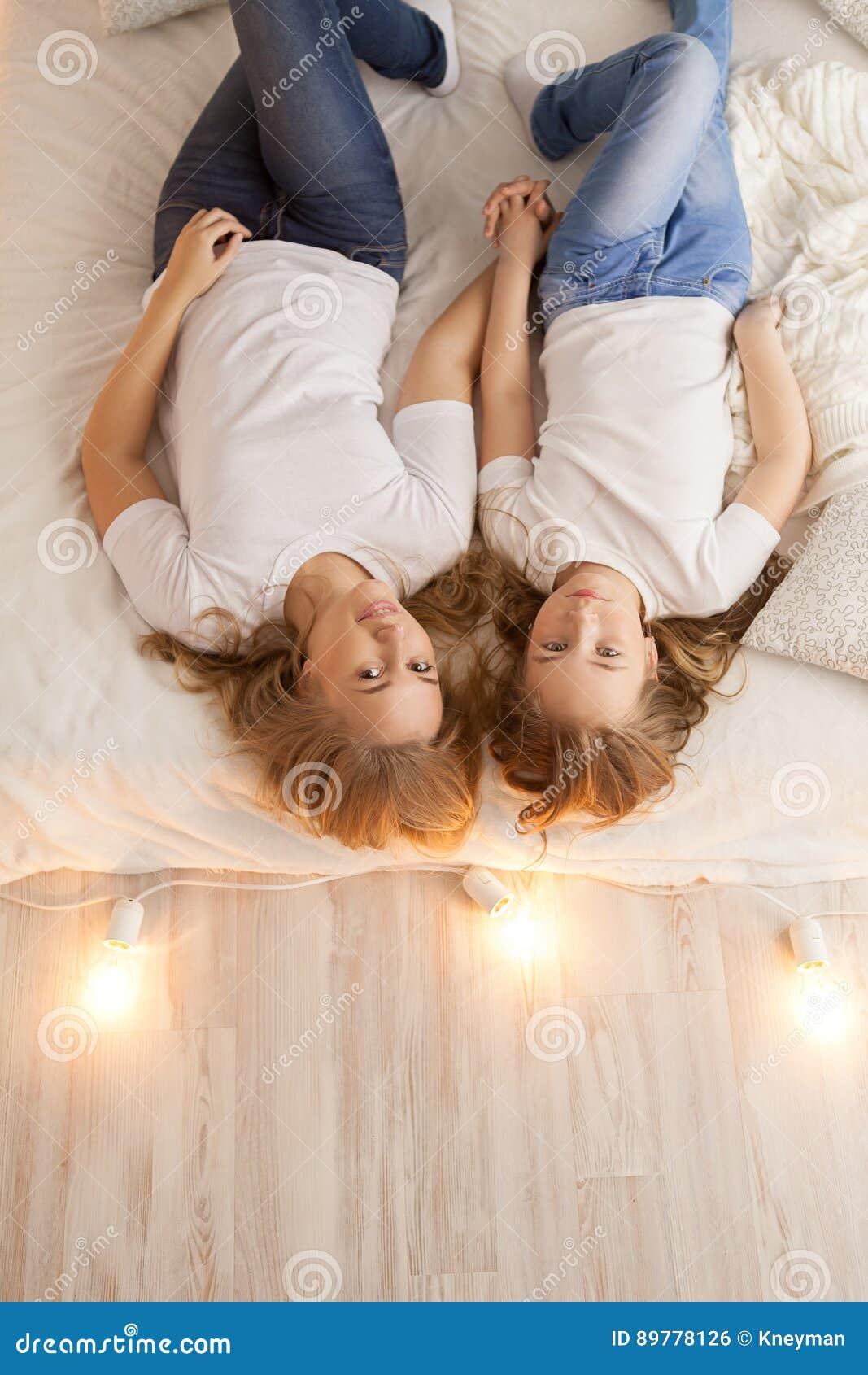 Endecha de la madre y de la hija en la cama y mirada en la cámara Visión desde arriba togetherness Interior del desván Copia-espa