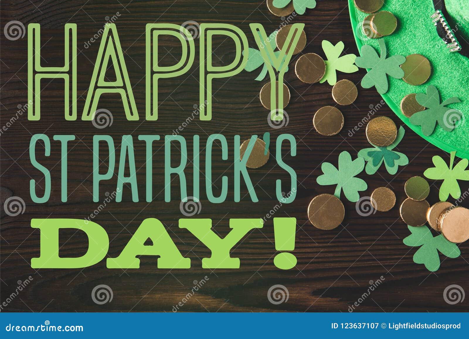 Endecha plana con el sombrero, las monedas y los tréboles verdes en superficie de madera con día feliz de los patricks del st