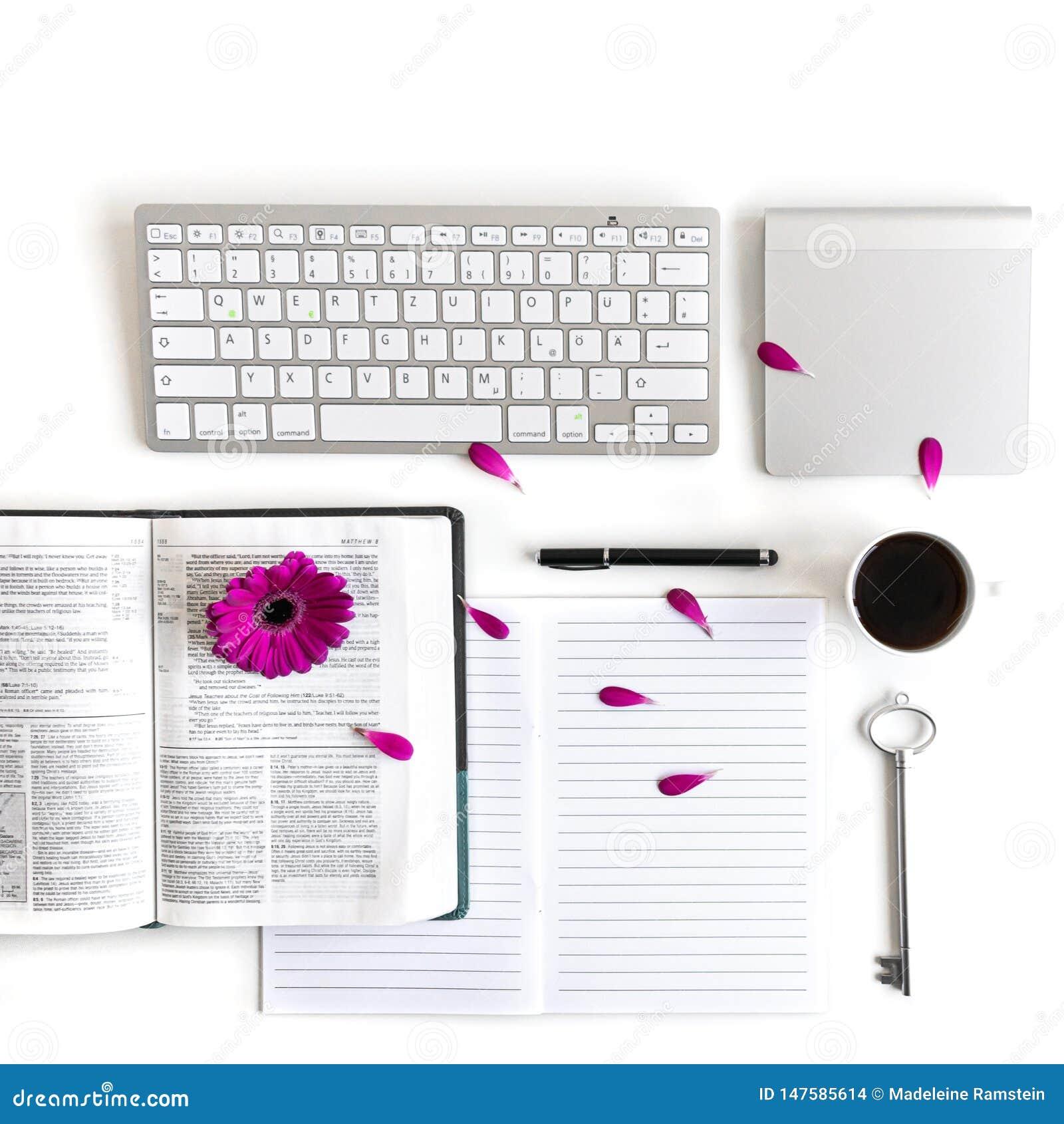 Endecha plana: cuaderno abierto, teclado, café, pluma negra y rosa, púrpuras, violette, flor roja del Gerbera con los pétalos