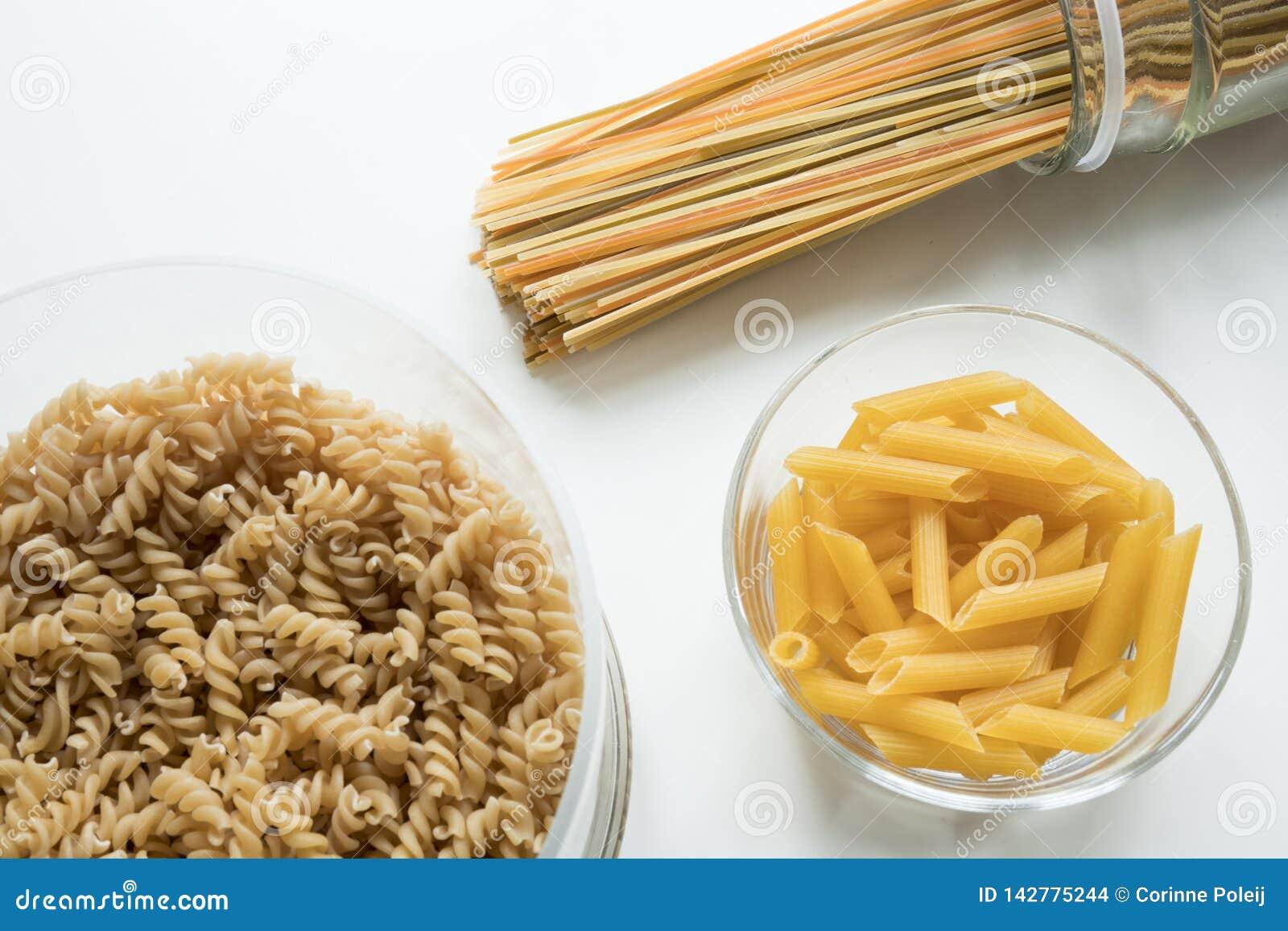 Endecha plana de espaguetis en un tarro, un fussili y un penne