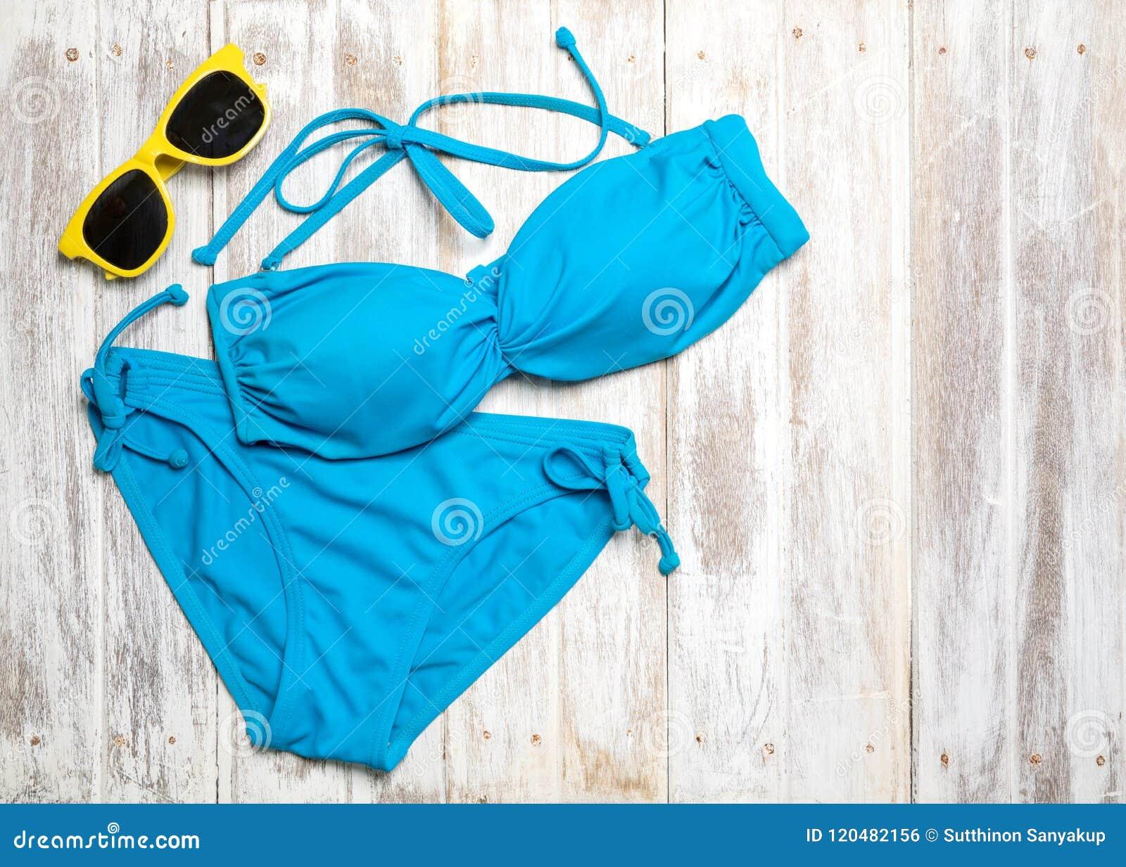 Endecha plana de los artículos del verano con el bikini y los accesorios coloridos en el fondo de madera blanco, concepto del ver