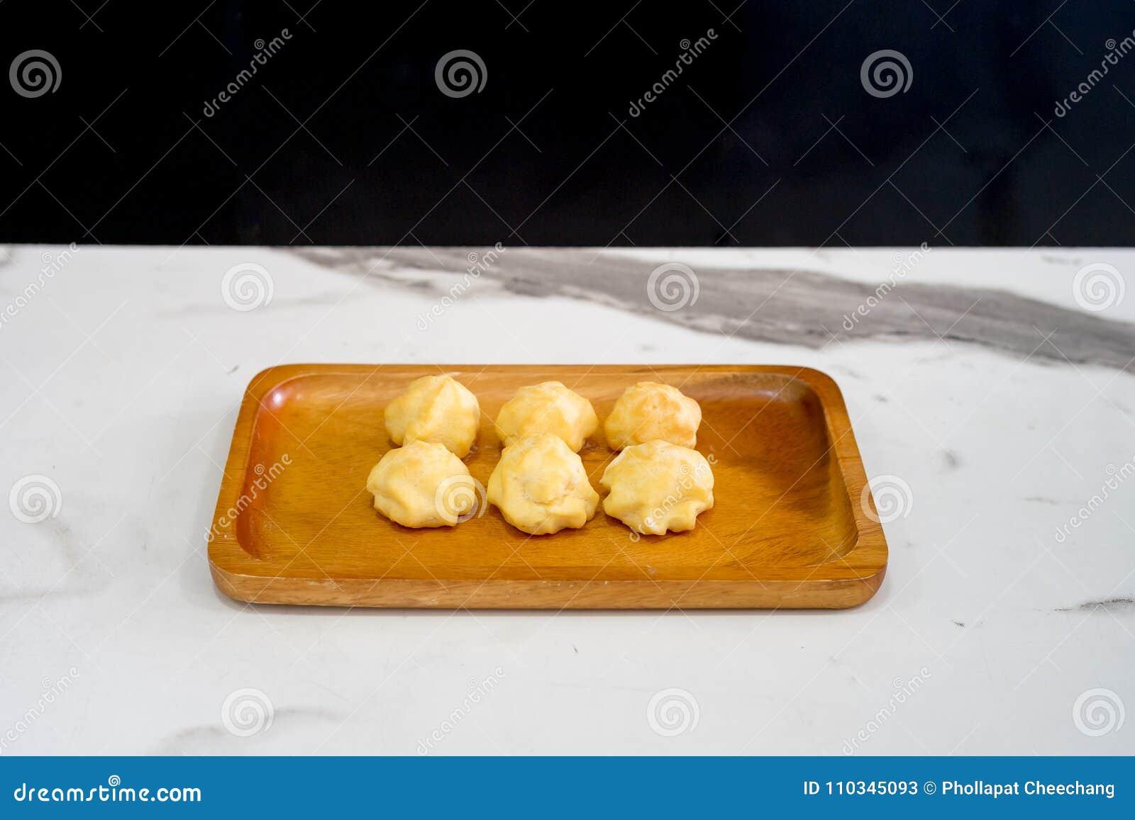 Endureça o eclair ou os sopros de creme ou o Profiterole na placa de madeira na tabela branca