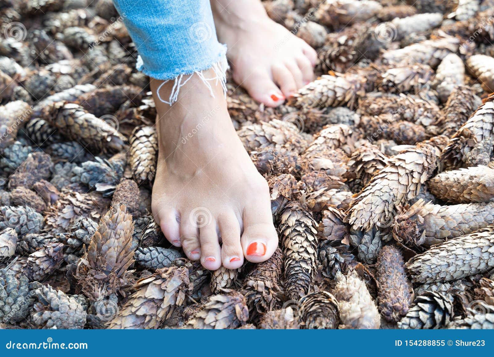 Endurecendo os pés com os pés descalços que andam às superfícies e às temperaturas diferentes de acordo com a filosofia de Sebast