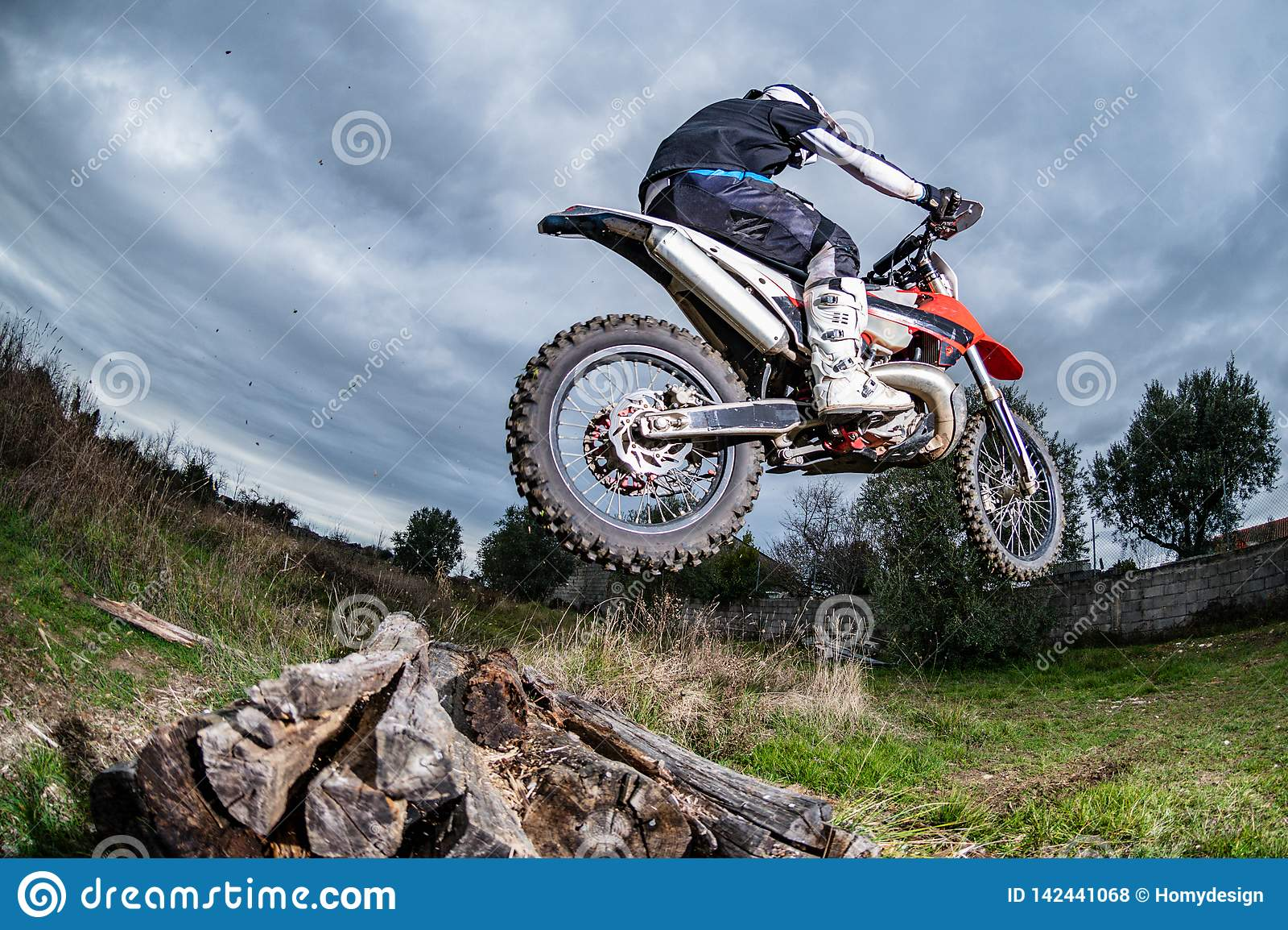 Man on muddy motocross scrambling motorcycle riding