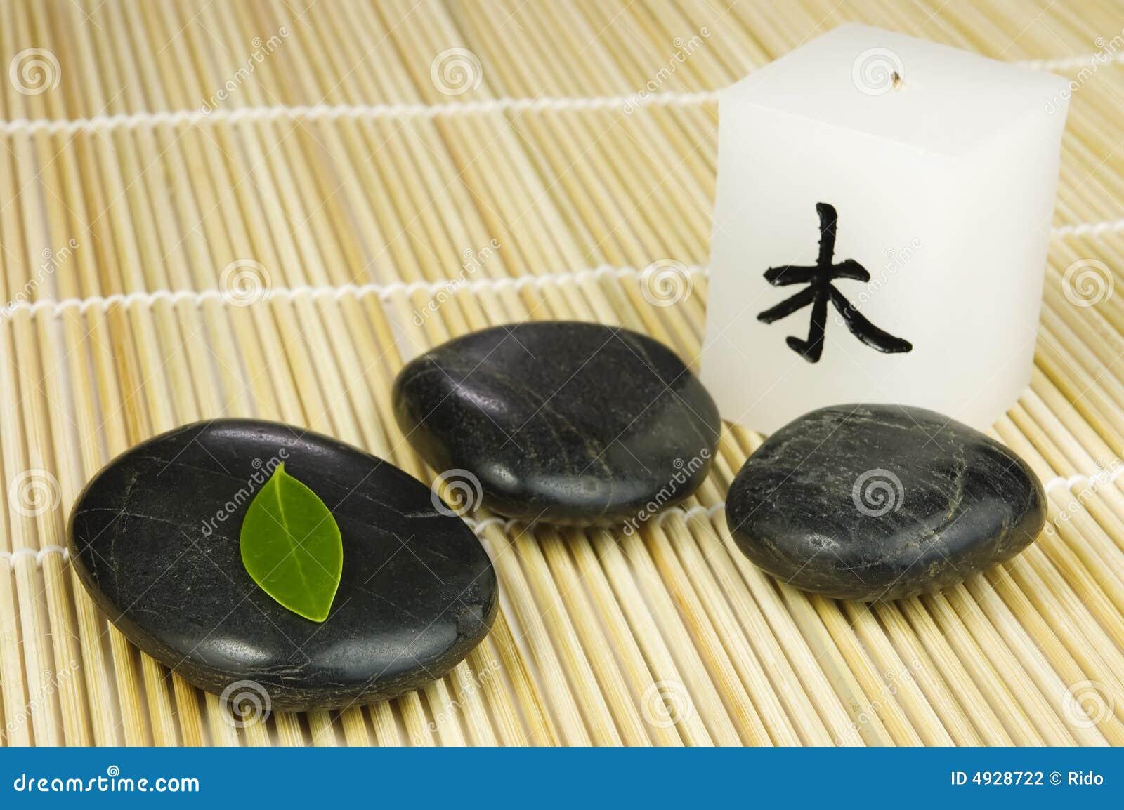 Enegreça seixos do zen, a folha verde e a vela japonesa