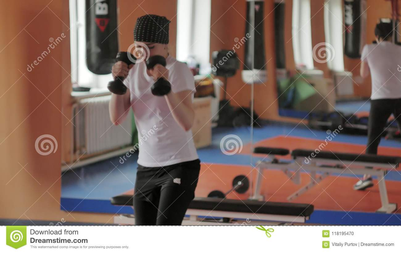An energetic woman in boxing in the gym, coaches in dumbbells