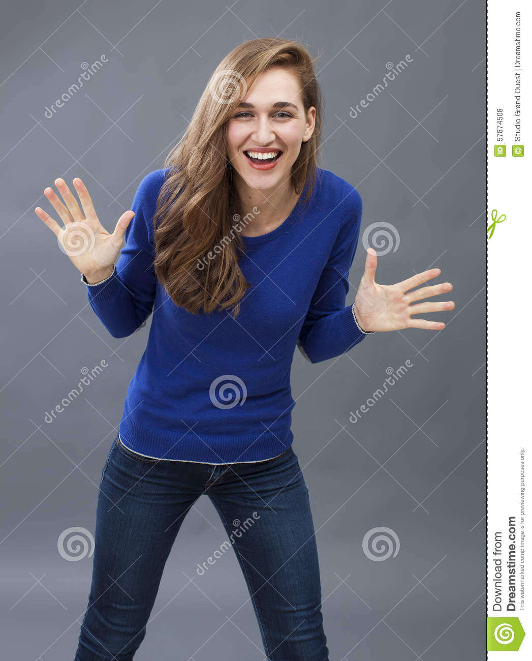 Energetic young woman smiling, having fun playing with her hands