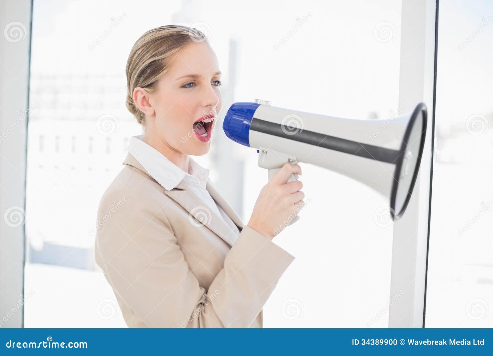 Energiczny blondynka bizneswoman krzyczy w megafonie