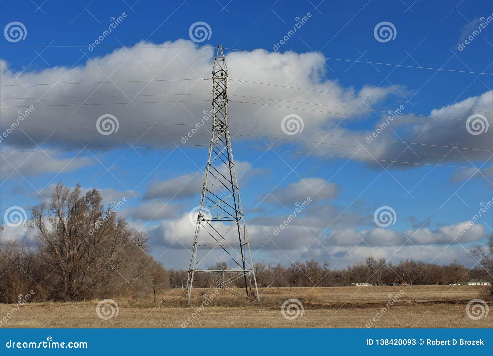 Energie-Turm auf einem Gebiet mit blauem Himmel und weißen Wolken