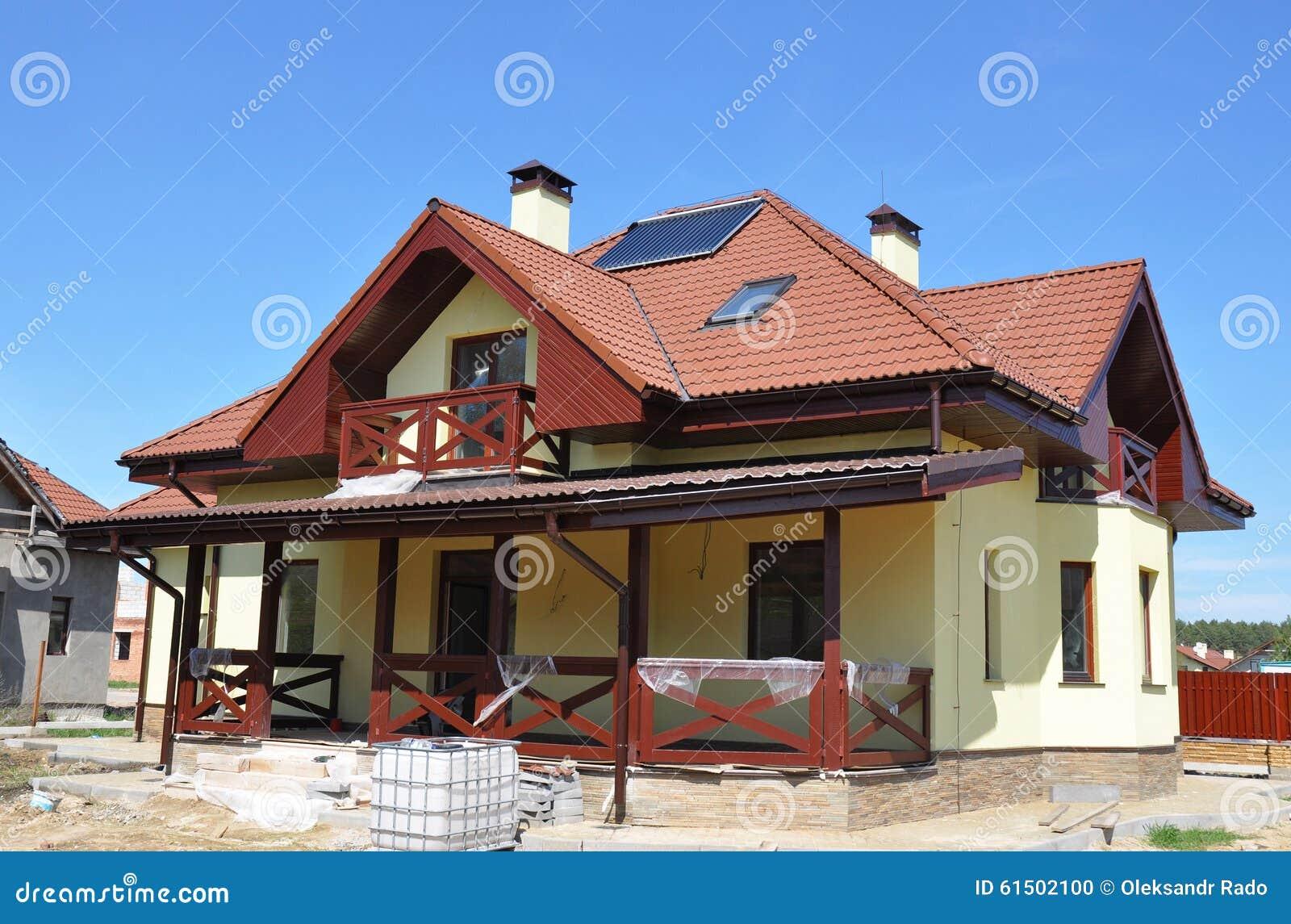Energy Efficiency Passive House Building Concept Outdoor. Closeup on Solar Water Heater, Dormers, Gutter, Solar Panels, Skylights
