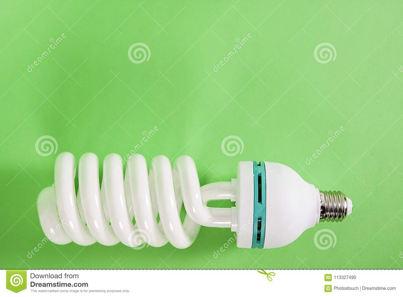 Energy saving spiral electric bulb on green background