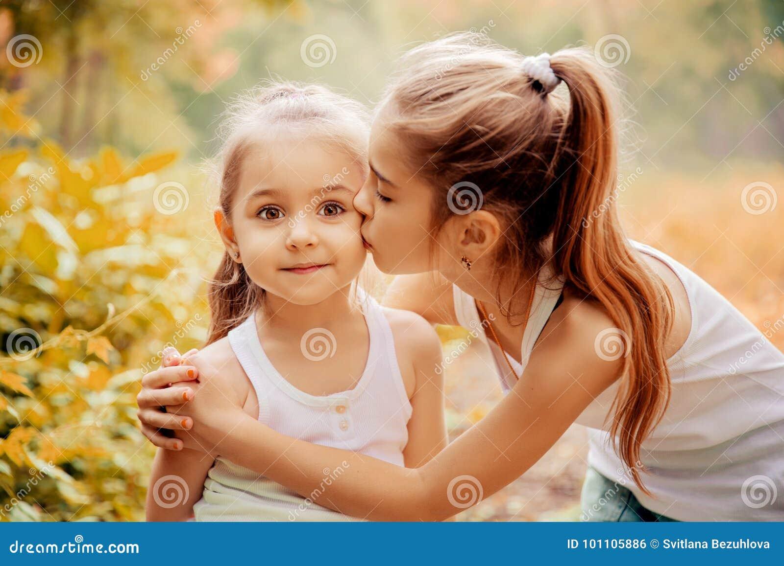 Enfance, famille, amitié et concept de personnes - deux soeurs heureuses d enfants étreignant dehors