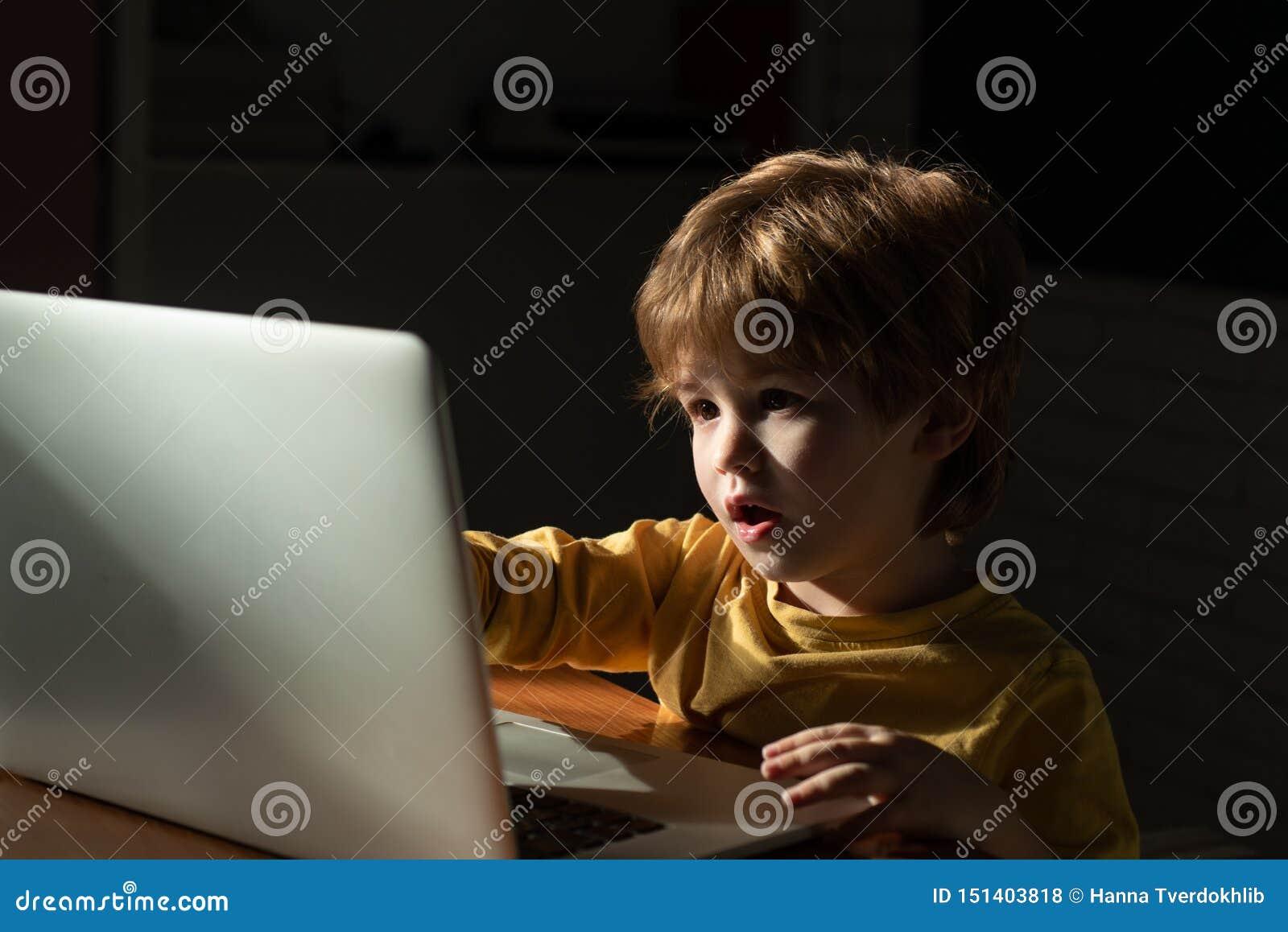 Enfant à la maison utilisant un ordinateur portable pour les bandes dessinées de observation L information intéressante sur l Int
