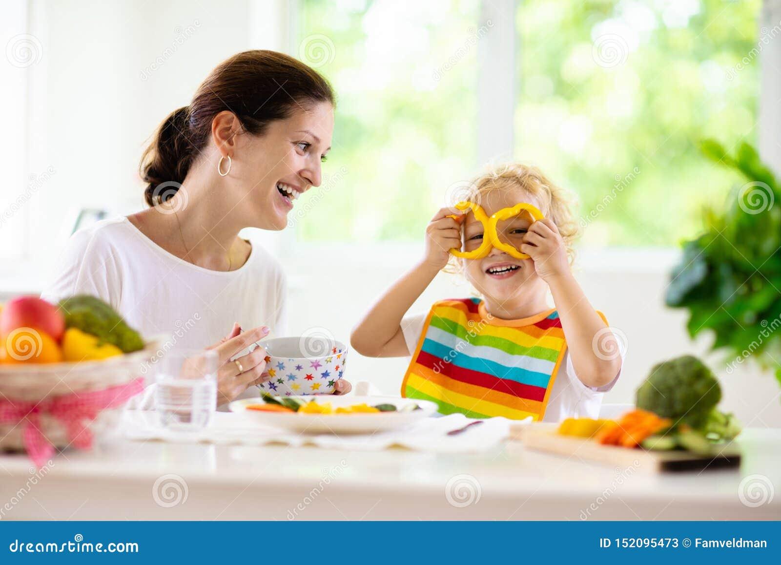 Enfant alimentant de m?re La maman alimente des l?gumes d enfant