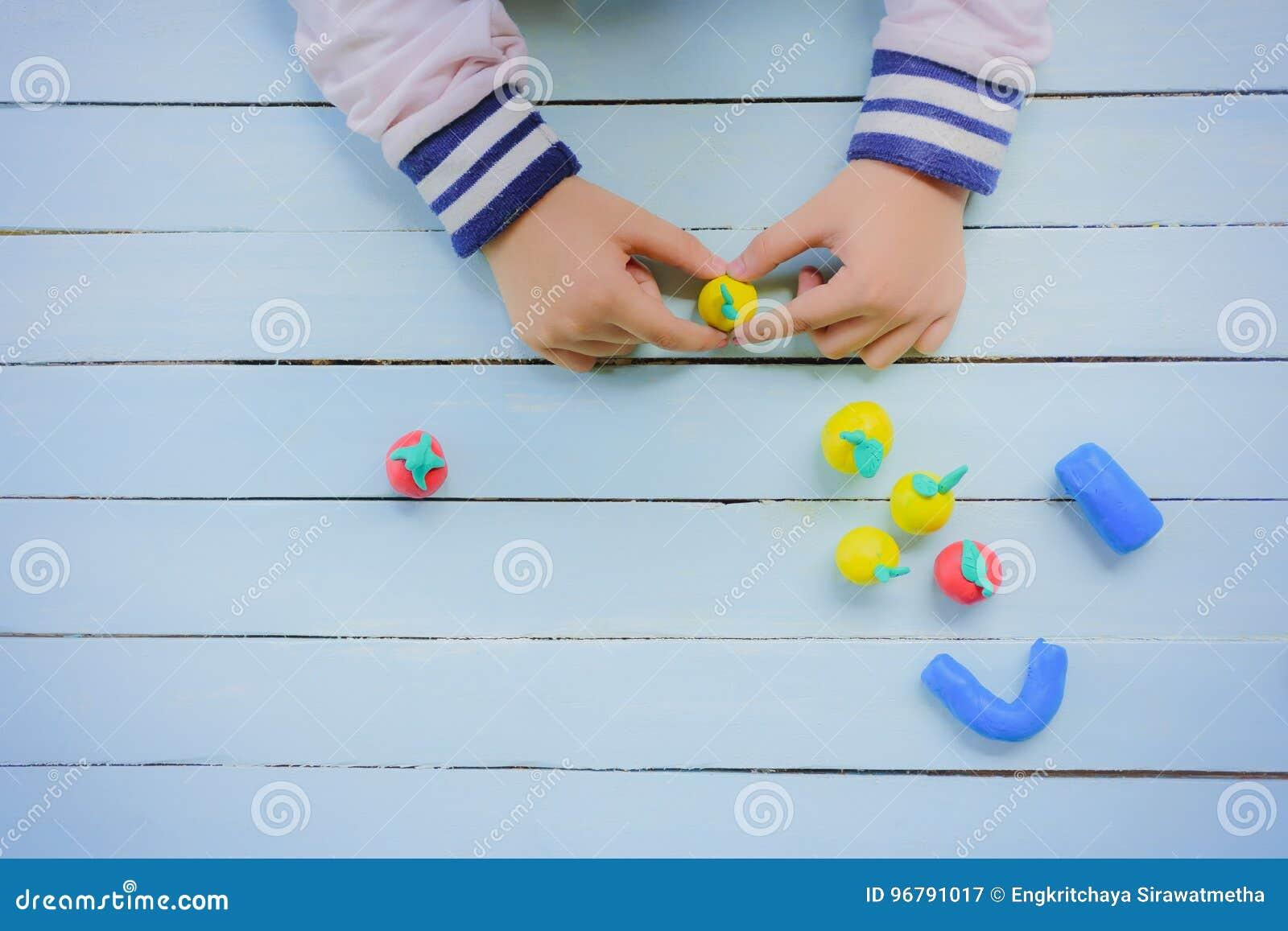 Enfant avec de l argile et créativité d utilisation pour faire le fruit, tel que l orange et etc.