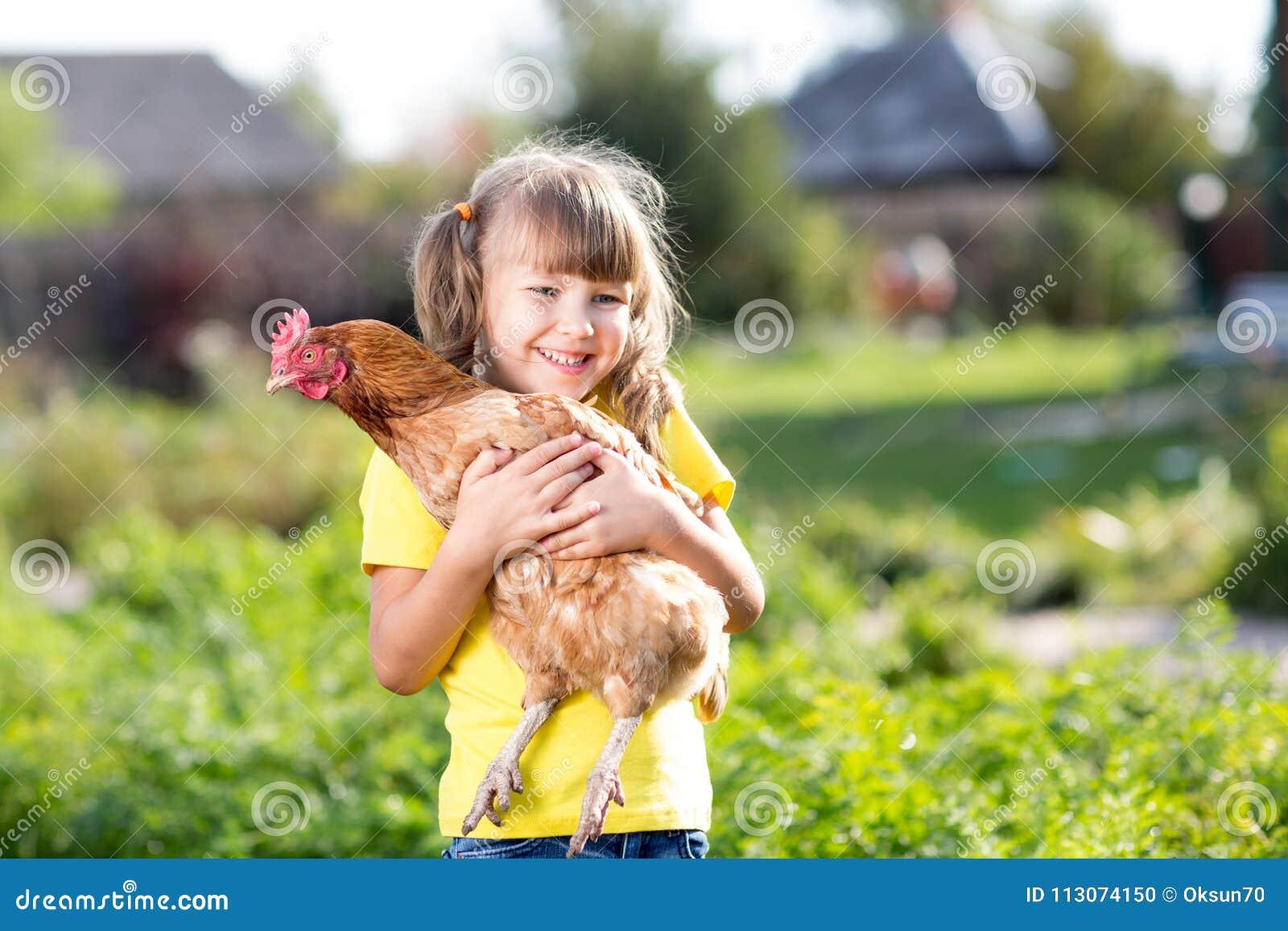 Enfant avec la poule dans des mains dans rural