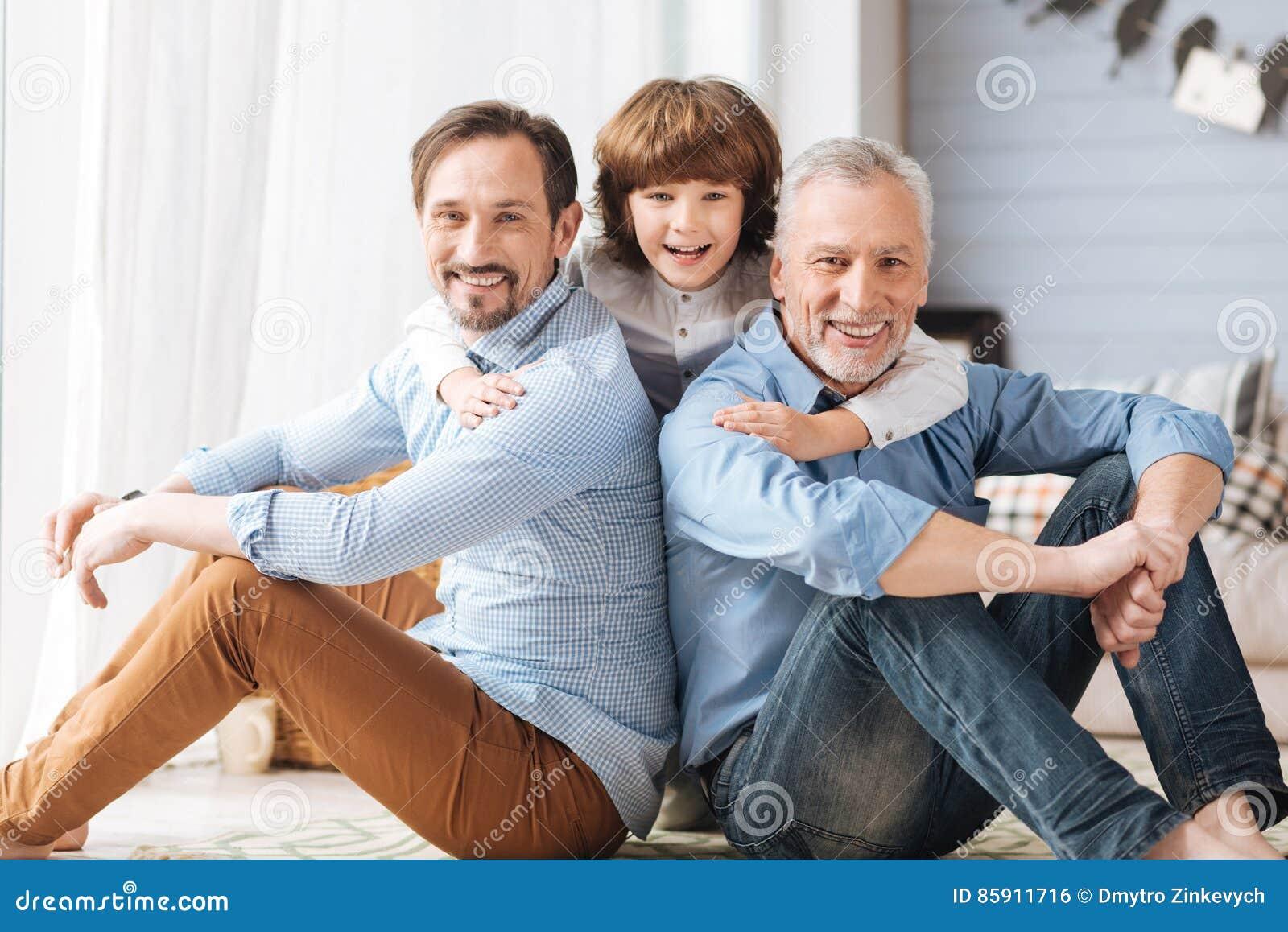 Enfant avec plaisir mignon étreignant son père et grand-père