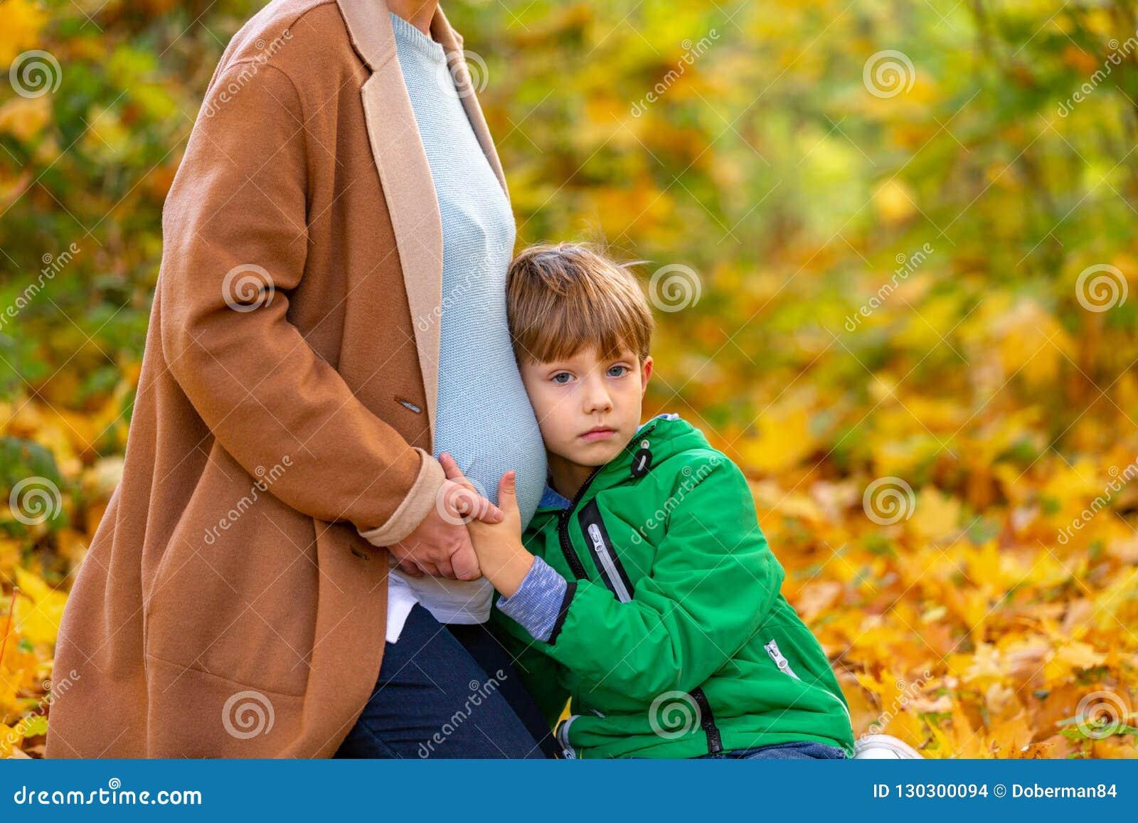 Enfant caucasien doux mignon écoutant le ventre de sa mère enceinte attendant le bébé secouant dans le ventre espérances