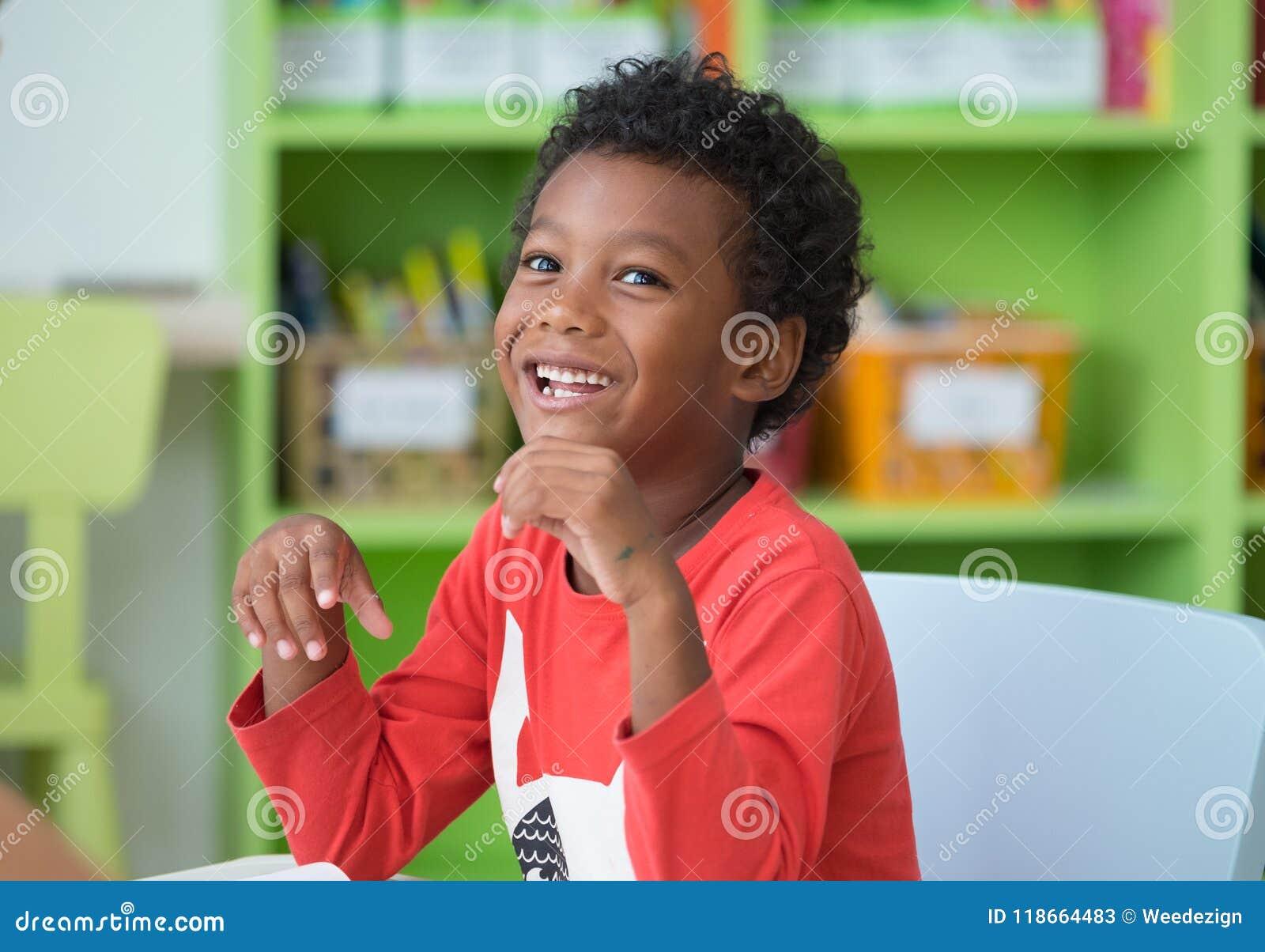 Enfant d appartenance ethnique d afro-américain souriant à la bibliothèque dans le kindergarte