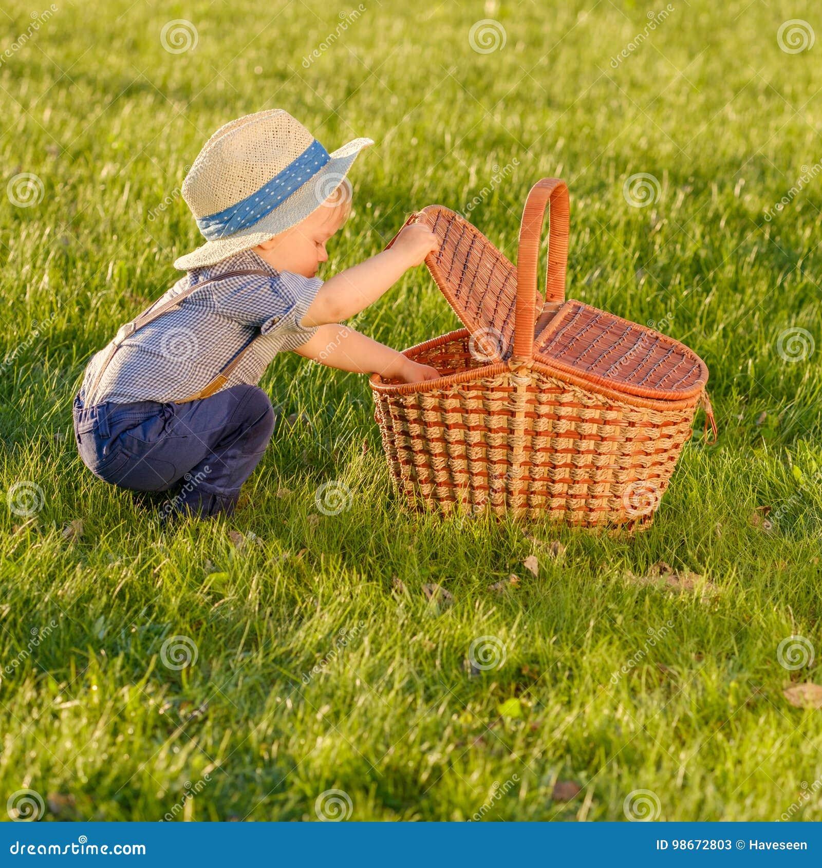 Enfant d enfant en bas âge dehors Un chapeau de paille de port de bébé garçon an regardant dans le panier de pique-nique