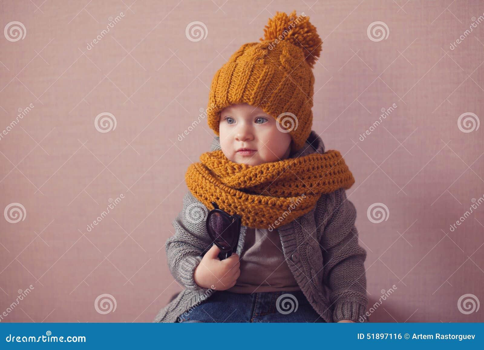 Enfant dans le chapeau tricoté de couleur de moutarde