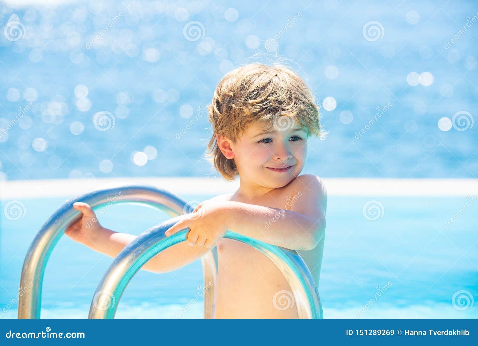 Enfant dans le regroupement Le garçon heureux descend à la piscine Le?ons de natation Petit enfant mignon de sourire dans la pisc
