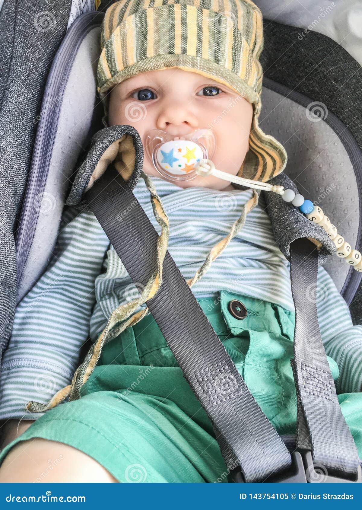 Enfant dans un siège de voiture avec le simulacre du bébé
